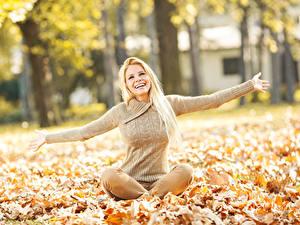 Fotos Herbst Blond Mädchen Sitzend Blattwerk Sweatshirt Hand Lächeln Mädchens