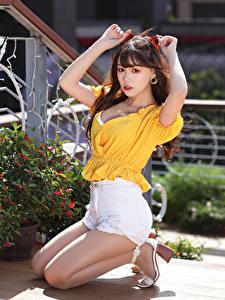 Fotos Asiatisches Braunhaarige Sitzend Shorts Bluse Hand Blick Mädchens