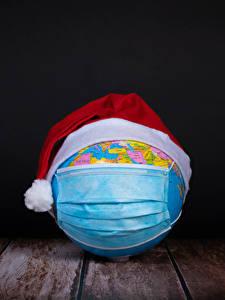 Fotos Neujahr Coronavirus Masken Bretter Schwarzer Hintergrund Globus Mütze