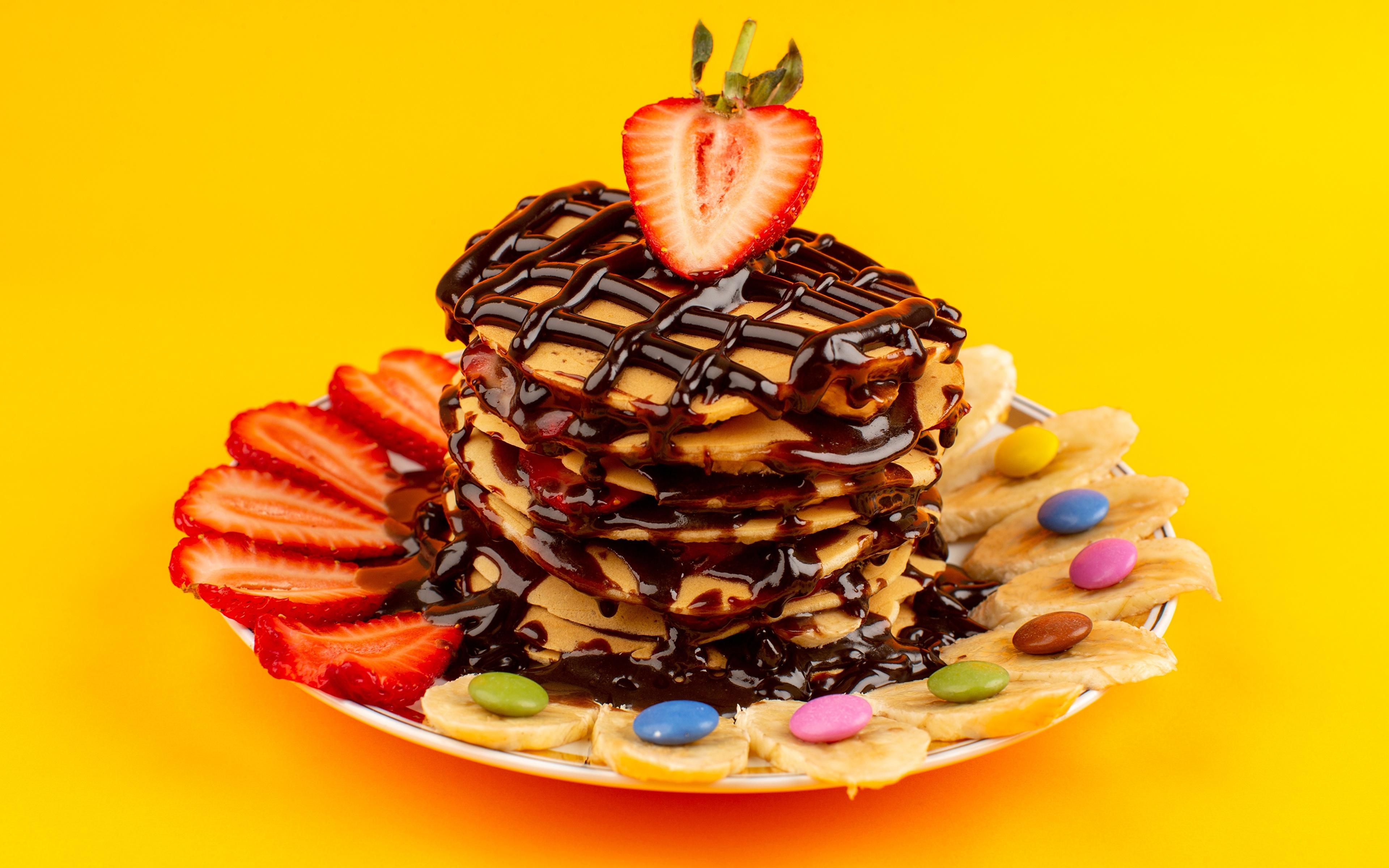 Фотография Драже Шоколад Блины Бананы Клубника Тарелка Продукты питания Цветной фон 3840x2400 Еда Пища тарелке