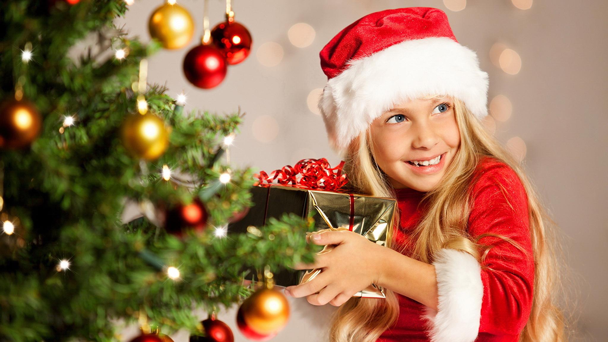 Bilder Kleine Mädchen Neujahr Lächeln Kinder Mütze Geschenke Ast Kugeln Starren 2048x1152 Blick