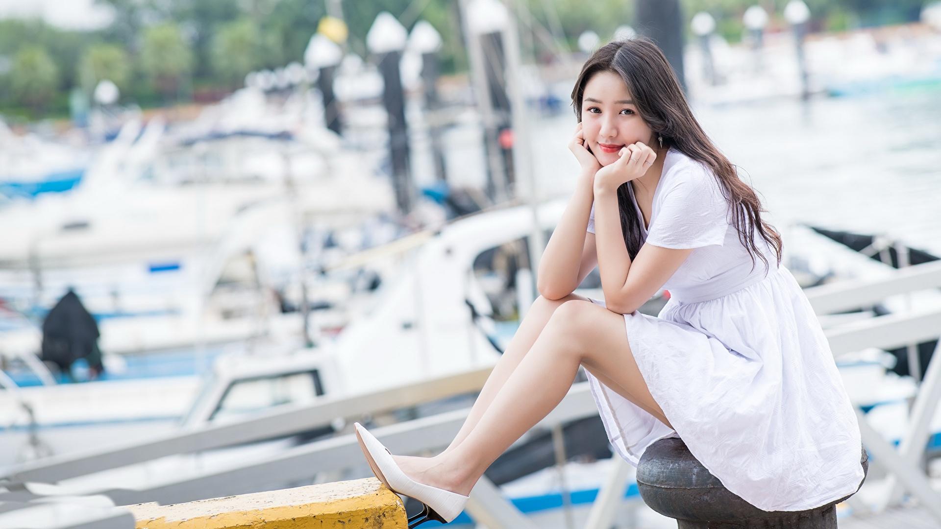 Immagine Ragazza capelli castani Bokeh giovane donna Asiatici Le gambe Seduto Braccia Abito 1920x1080 sfondo sfocato ragazza Ragazze giovani donne asiatico sedute seduta Le mani Vestito