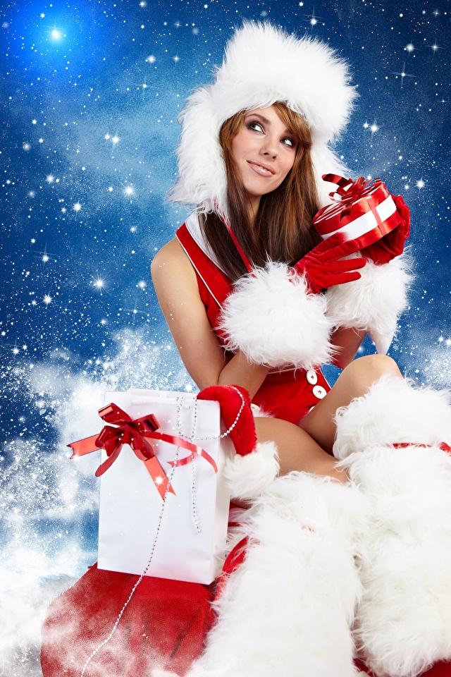 Hintergrundbilder Neujahr Braunhaarige Mütze Mädchens Geschenke Sitzend 640x960 Braune Haare sitzt sitzen