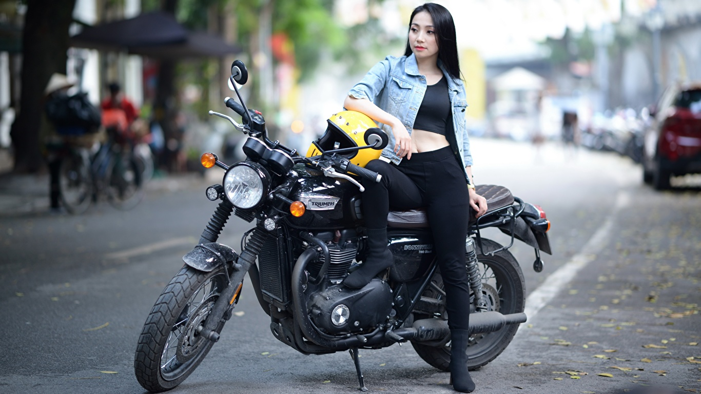 Fotos Triumph Motorcycles Ltd. Brünette Helm unscharfer Hintergrund Mädchens Motorräder Asiatische 1366x768 Bokeh Motorrad junge frau junge Frauen Asiaten asiatisches