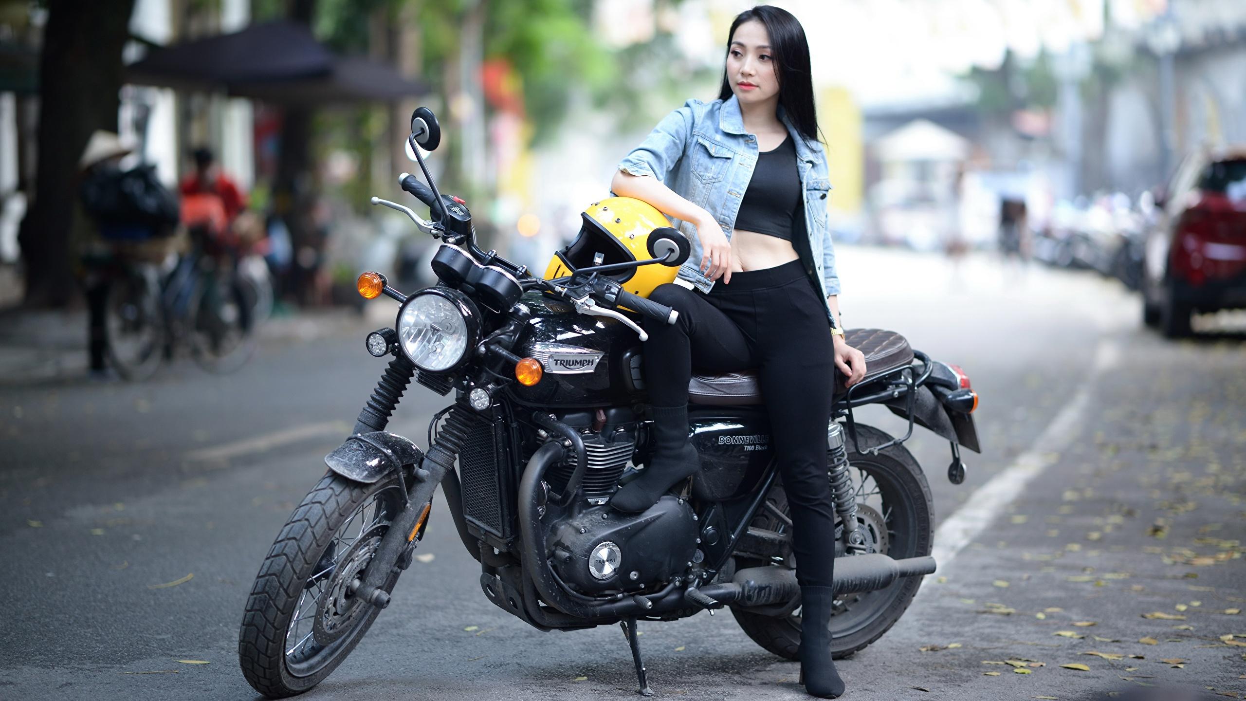 Fotos Triumph Motorcycles Ltd. Brünette Helm unscharfer Hintergrund Mädchens Motorräder Asiatische 2560x1440 Bokeh Motorrad junge frau junge Frauen Asiaten asiatisches