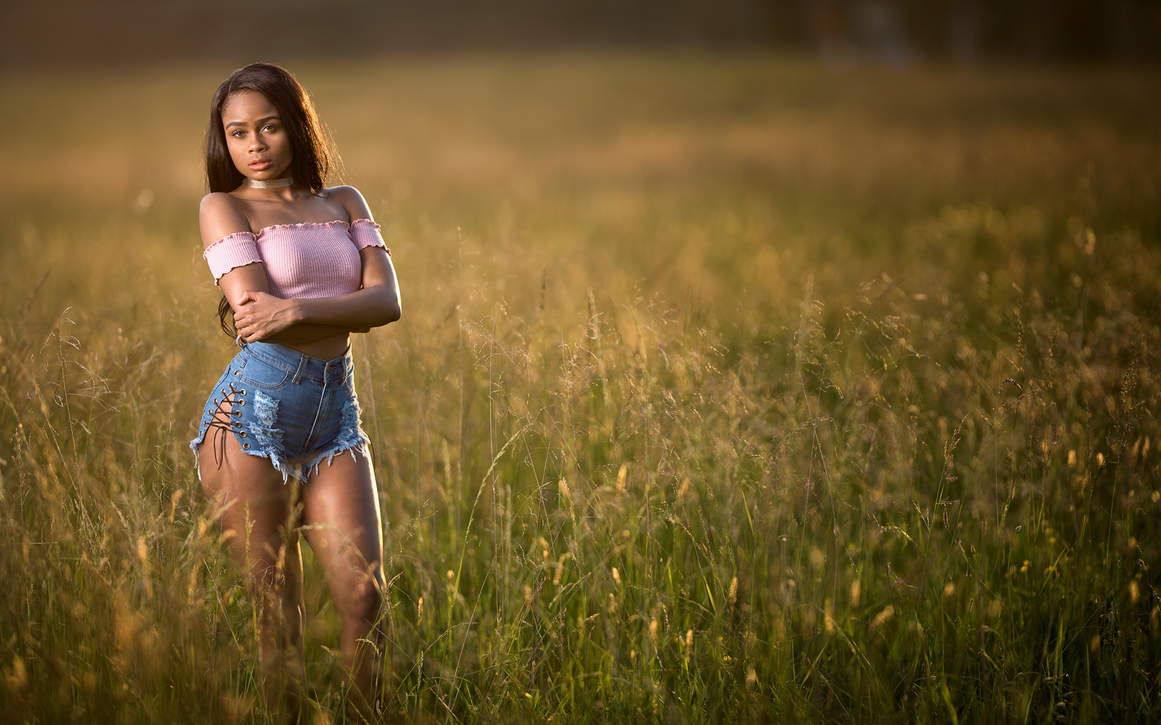 Image Brunette girl Bokeh Girls Negroid Grass Hands Shorts 3840x2400 blurred background female young woman