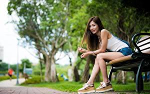 Bilder Asiaten Bank (Möbel) Unscharfer Hintergrund Braune Haare Sitzend Hand Bein junge frau