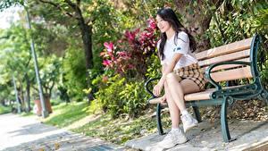 Fotos Asiaten Bank (Möbel) Unscharfer Hintergrund Brünette Lächeln Sitzt Rock Bein Sportschuhe junge frau