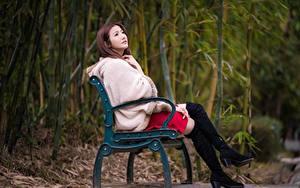 Fotos Asiatische Bank (Möbel) Braune Haare Sitzt Bein Stiefel Pelzmantel junge frau