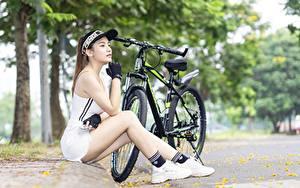 Fotos Asiaten Fahrrad Baseballcap Sitzend Hand Handschuh Bein Sportschuhe Mädchens