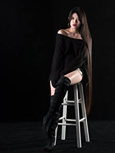 Photo Asian Black background Chair Sitting Wearing boots Legs Sweater Hair Glance female