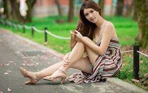 Bilder Asiatisches Bokeh Braunhaarige Kleid Sitzen Hand Bein High Heels Mädchens