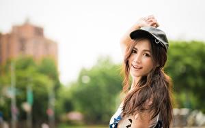 Desktop hintergrundbilder Asiatisches Bokeh Braunhaarige Starren Hand Baseballmütze Lächeln Mädchens