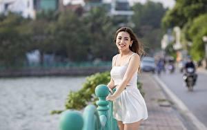 Bilder Asiaten Unscharfer Hintergrund Braune Haare Blick Lächeln Hand Rock Mädchens