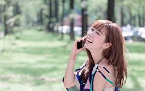 Fotos Asiaten Bokeh Braune Haare Lachen Hand Telefon junge Frauen