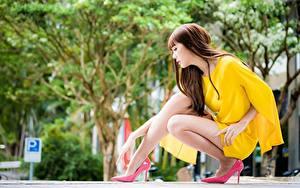 Fotos Asiatische Bokeh Braunhaarige Sitzt Hand Bein Stöckelschuh junge frau