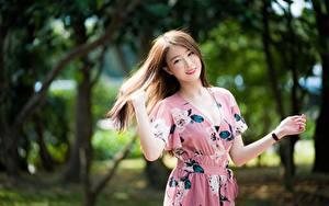Bilder Asiatisches Unscharfer Hintergrund Braune Haare Lächeln Hand Kleid junge Frauen