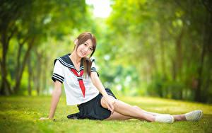Fotos Asiaten Unscharfer Hintergrund Sitzt Gras Lächeln Uniform Krawatte Schülerin Mädchens