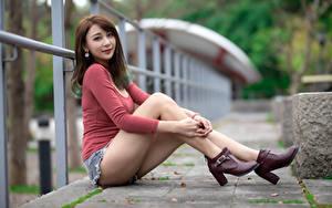 Fotos Asiatisches Bokeh Sitzen Bein Shorts Braune Haare Blick High Heels Zaun  Mädchens