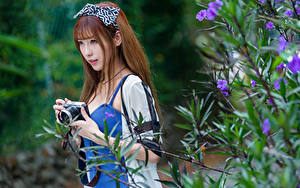 Fotos Asiaten Ast Unscharfer Hintergrund Fotoapparat Starren Braune Haare Mädchens