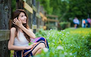 Bilder Asiaten Braune Haare Bokeh Lächeln Gras Hand Sitzen junge frau