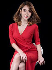 Fotos Asiatische Braunhaarige Kleid Rot Sitzt Blick Schwarzer Hintergrund junge frau