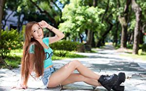 Fotos Asiatische Braune Haare Sitzend Lächeln Shorts Hand Bein Boots junge frau