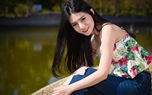Bilder Asiatische Brünette Blick Lächeln Hand Sitzend Jeans Bokeh junge frau