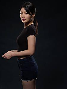 Hintergrundbilder Asiatisches Brünette Shorts Hand Starren Schwarzer Hintergrund Mädchens