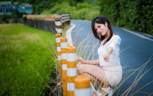 Fotos Asiatische Brünette Lächeln Unscharfer Hintergrund Hand Bein Sitzt junge Frauen