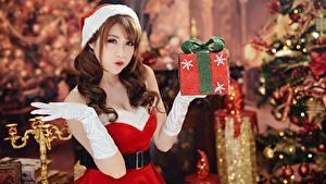 Bilder Asiatische Neujahr Braune Haare Uniform Hand Handschuh Geschenke Unscharfer Hintergrund Mädchens