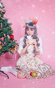 Hintergrundbilder Asiatische Neujahr Sitzend Kleid Christbaum Kugeln Farbigen hintergrund Blick Mädchens