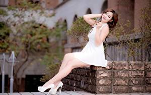 Bilder Asiatische Kleid Braune Haare Sitzt Hand Bein Stöckelschuh Bokeh junge frau