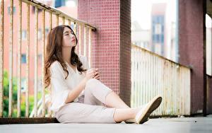 Bilder Asiatisches Zaun Bokeh Braune Haare Sitzt Bein junge Frauen