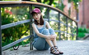 Hintergrundbilder Asiatische Zaun Braunhaarige Baseballcap Sitzen Hand Bein Unscharfer Hintergrund junge Frauen