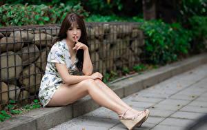 Desktop hintergrundbilder Asiatisches Finger Gestik Sitzend Bein Kleid Starren Braune Haare junge frau