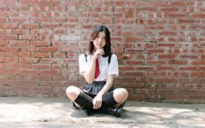 Desktop hintergrundbilder Asiatisches Gestik Wand Aus backsteinen Sitzt Brünette Krawatte Hand Bein Long Socken junge frau