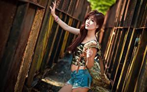 Fotos Asiatisches Handtasche Bokeh Zaun Rotschopf Starren Hand Shorts junge frau