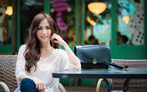 Bilder Asiatische Handtasche Bokeh Sitzend Blick Lächeln Hand Braunhaarige Mädchens