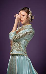 Desktop hintergrundbilder Asiatische Schmuck Posiert Kleid Hand Starren Farbigen hintergrund Mädchens
