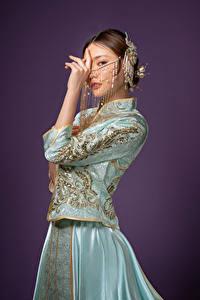 Hintergrundbilder Asiatische Schmuck Posiert Kleid Hand Starren Farbigen hintergrund Mädchens
