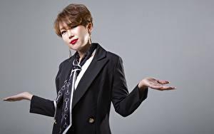 Fotos Asiaten Grauer Hintergrund Braune Haare Starren Hand Krawatte Korean junge frau