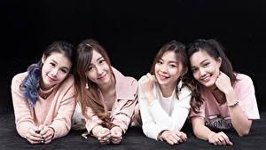 Bilder Asiatische Liegen Vier 4 Lächeln Starren Schwarzer Hintergrund junge Frauen