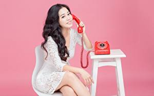 Hintergrundbilder Asiatische Rosa Hintergrund Brünette Telefon Sitzend Lächeln Hand Kleid junge frau