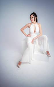 Bilder Asiaten Posiert Sitzend High Heels Grauer Hintergrund Kleid junge frau