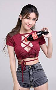 Bilder Asiatische Pose Lächeln Shorts Flasche Unterhemd Blick Grauer Hintergrund Mädchens