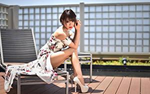 Bilder Asiaten Sitzt Kleid Bein High Heels Starren junge Frauen