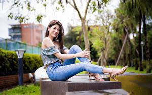 Fotos Asiatisches Sitzend Bein Jeans Lächeln Blick junge Frauen