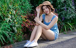 Bilder Asiatische Sitzt Bein Shorts Unterhemd Der Hut Starren Hübsch Mädchens