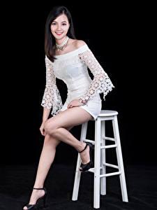 Bilder Asiaten Lächeln Bein Kleid Posiert Starren Schwarzer Hintergrund